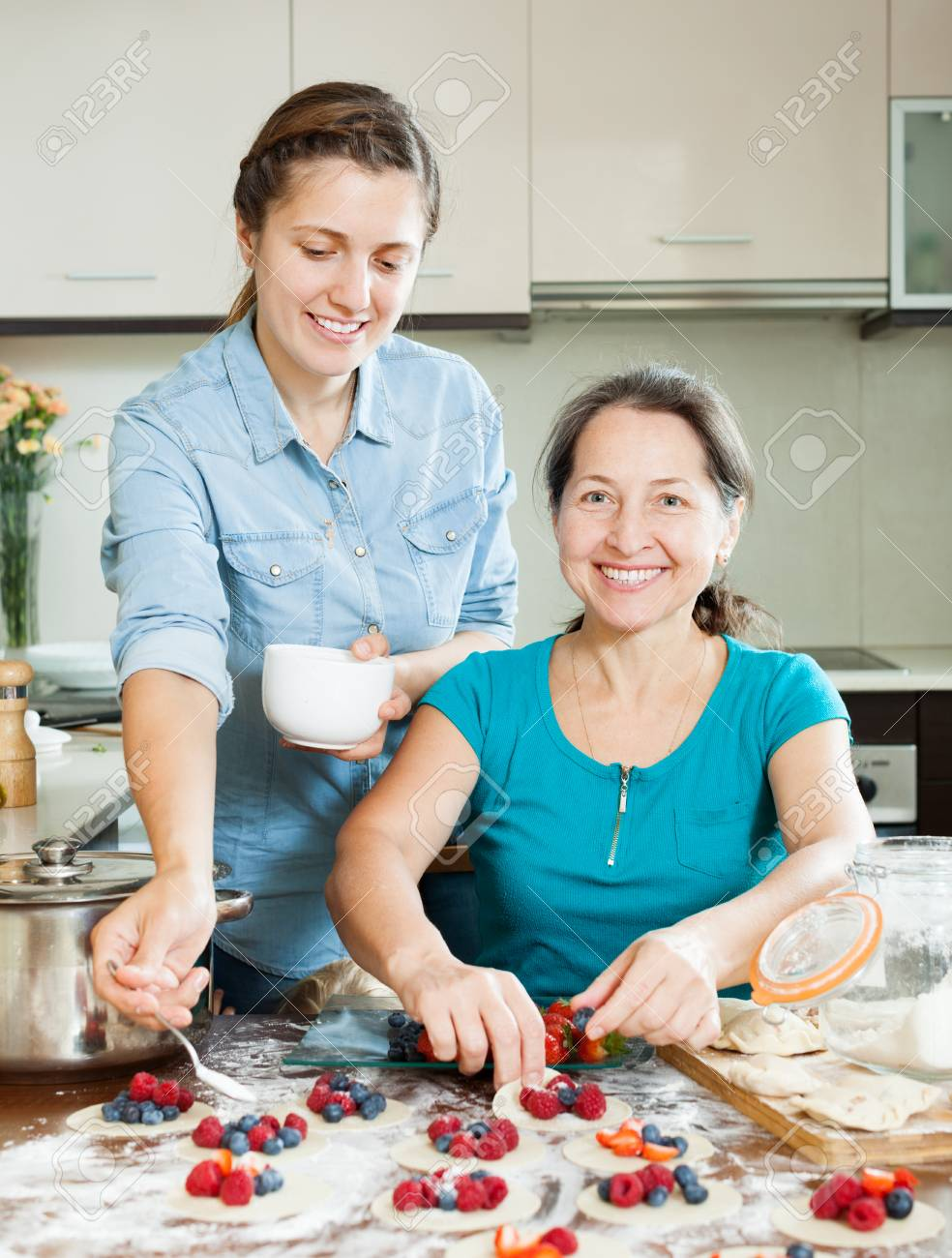 Smiling Women Making Sweet Pies With Berries Together At Home ...