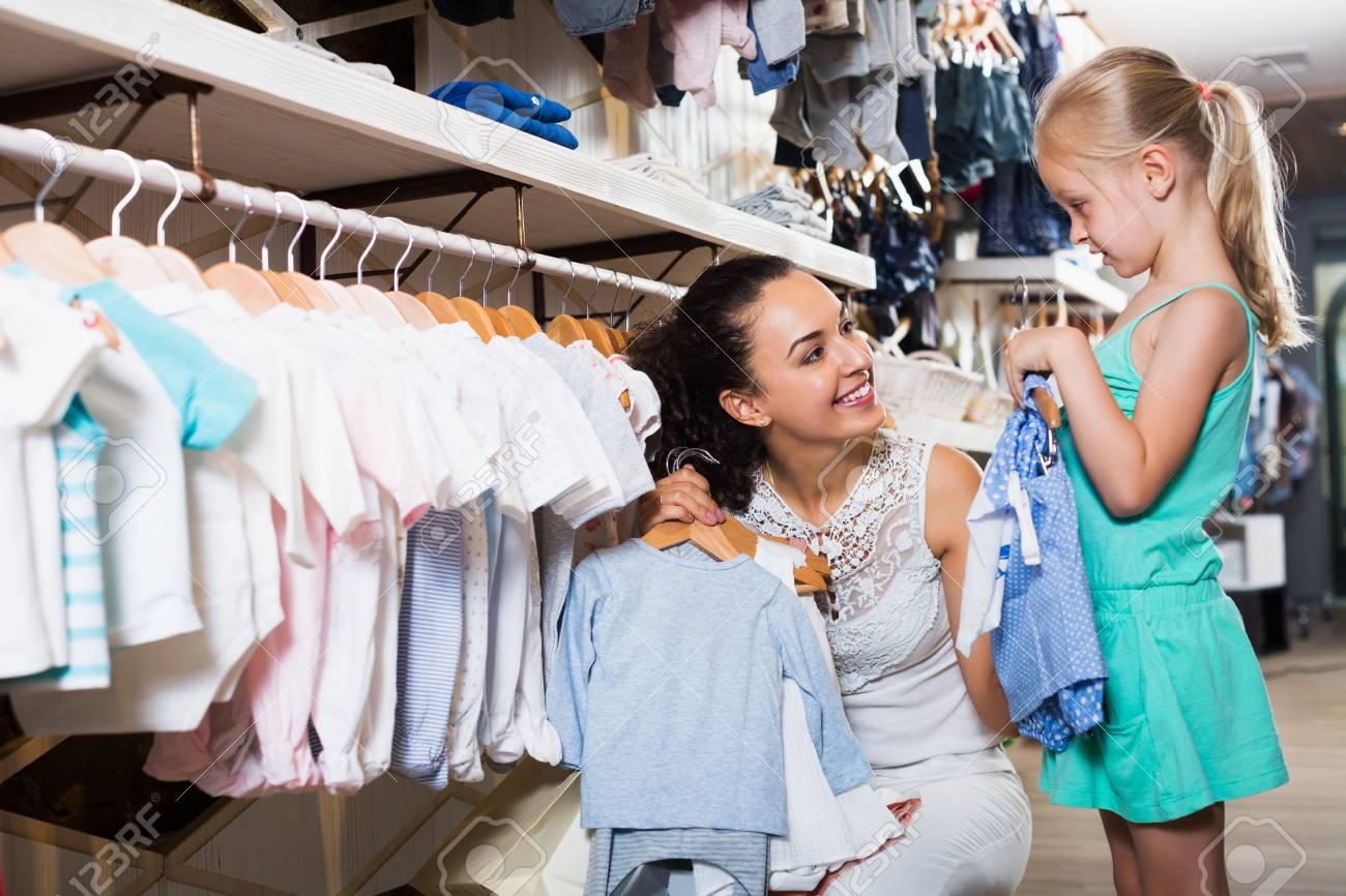 34d33186c9a8 Foto de archivo - Madre morena positiva con la hija comprar ropa de los niños  en color azul en la tienda