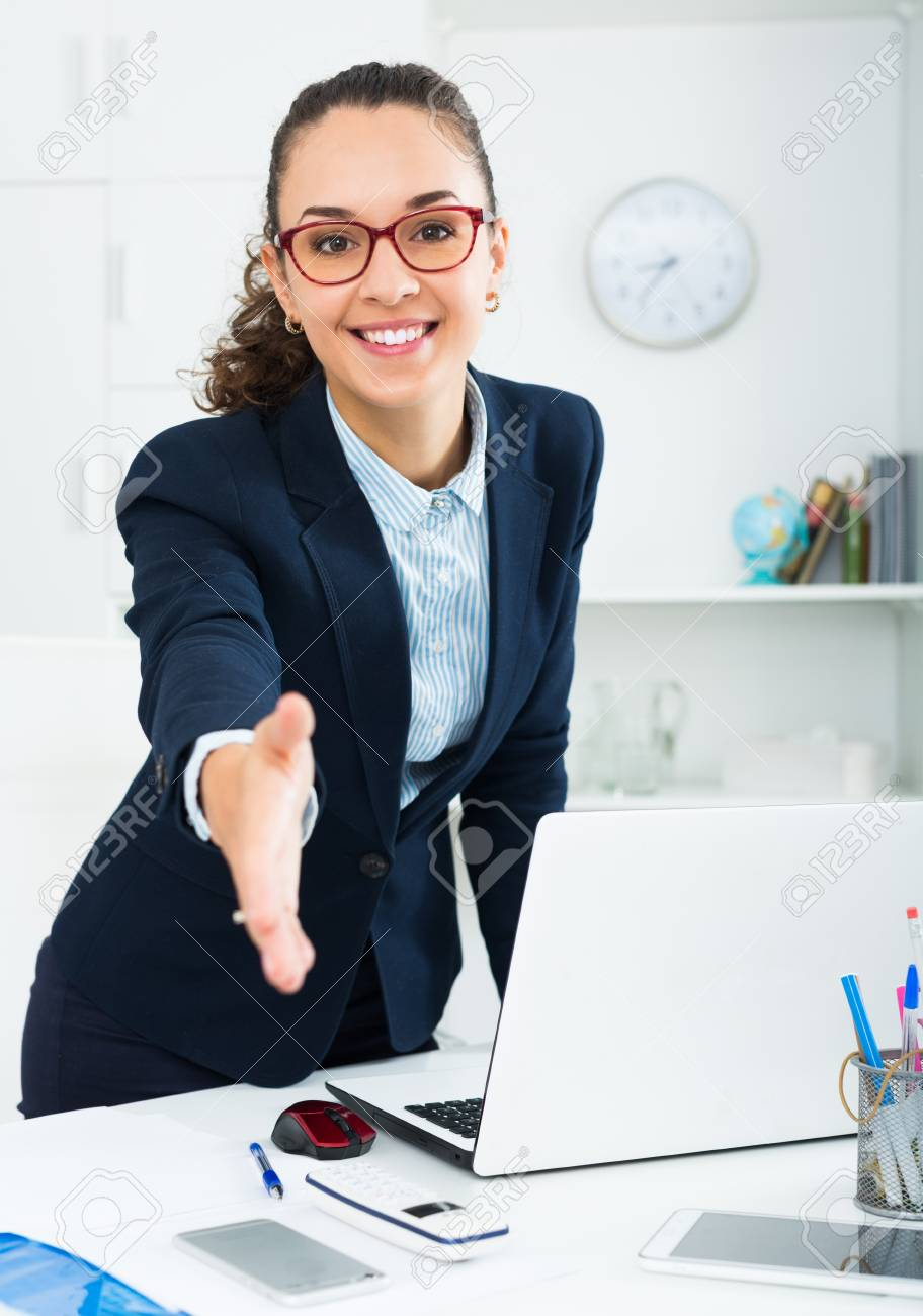 Business lady with dark hair greeting someone at desk stock photo business lady with dark hair greeting someone at desk stock photo 65752727 m4hsunfo