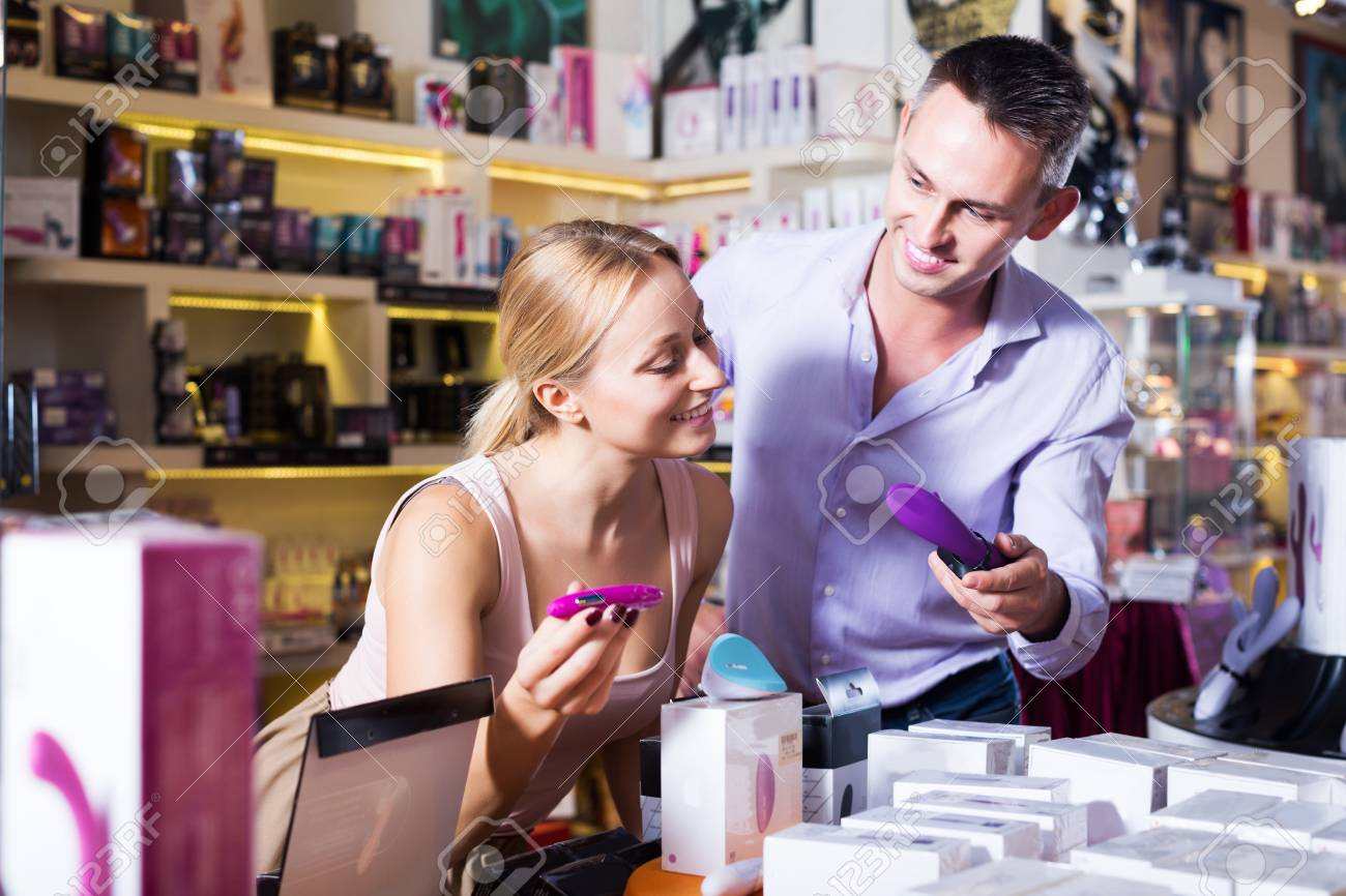 Portrait of positive adult couple choosing erotic toys in sex shop Stock  Photo - 65833651