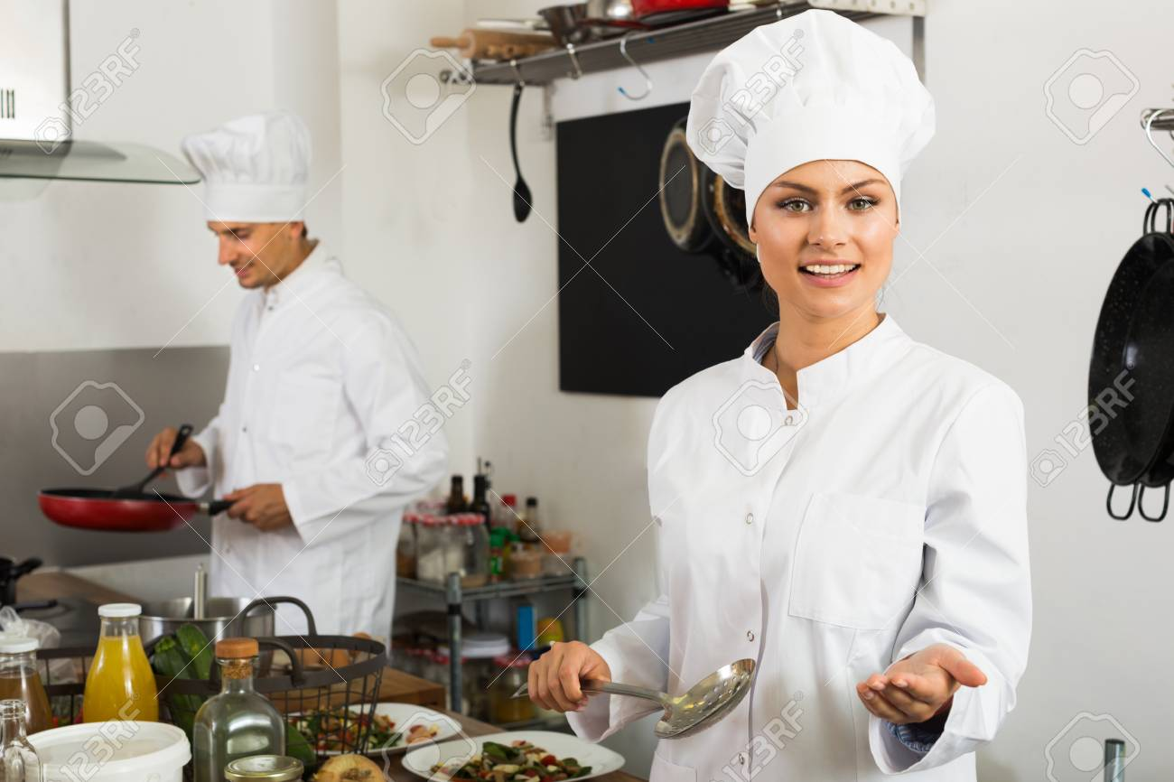 Glad Young Woman Chef Cooking Food At Restaurant\'s Kitchen Stock ...