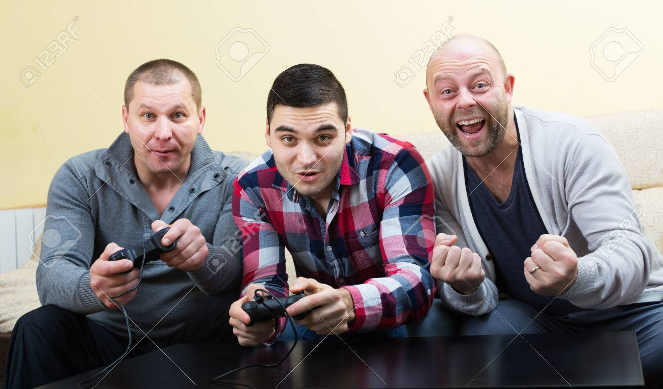 Happy men relaxing with video game and laughing at home