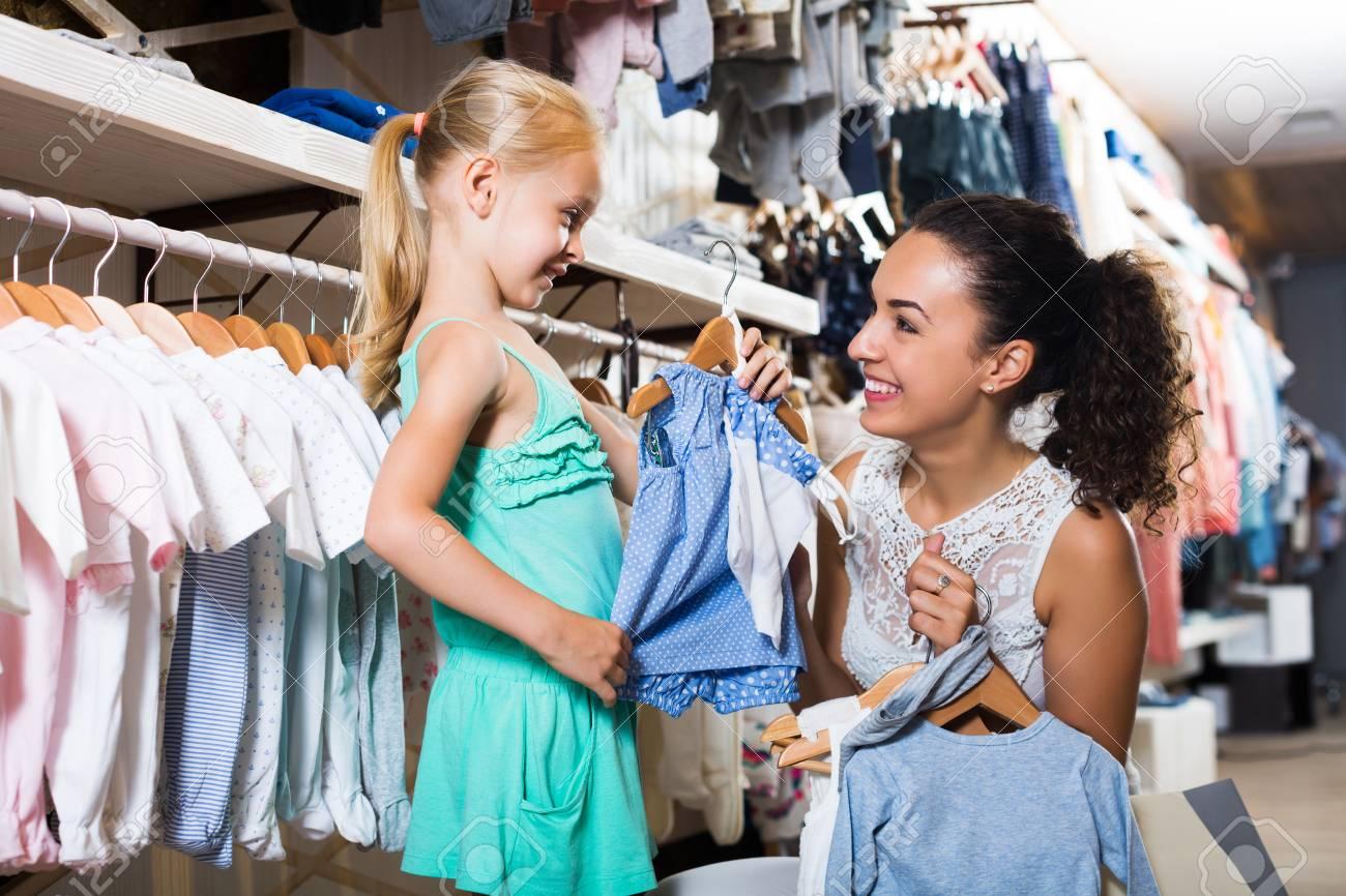 5007464fc91 Foto de archivo - Madre con la hija morena comprar ropa de niños en color  azul en la tienda