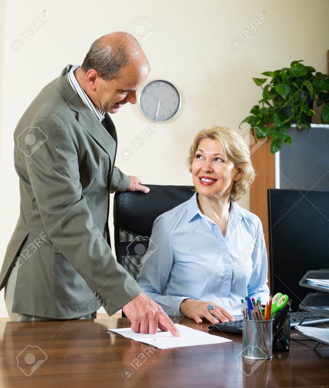 co-worker talking with mature female secretary in office stock photo