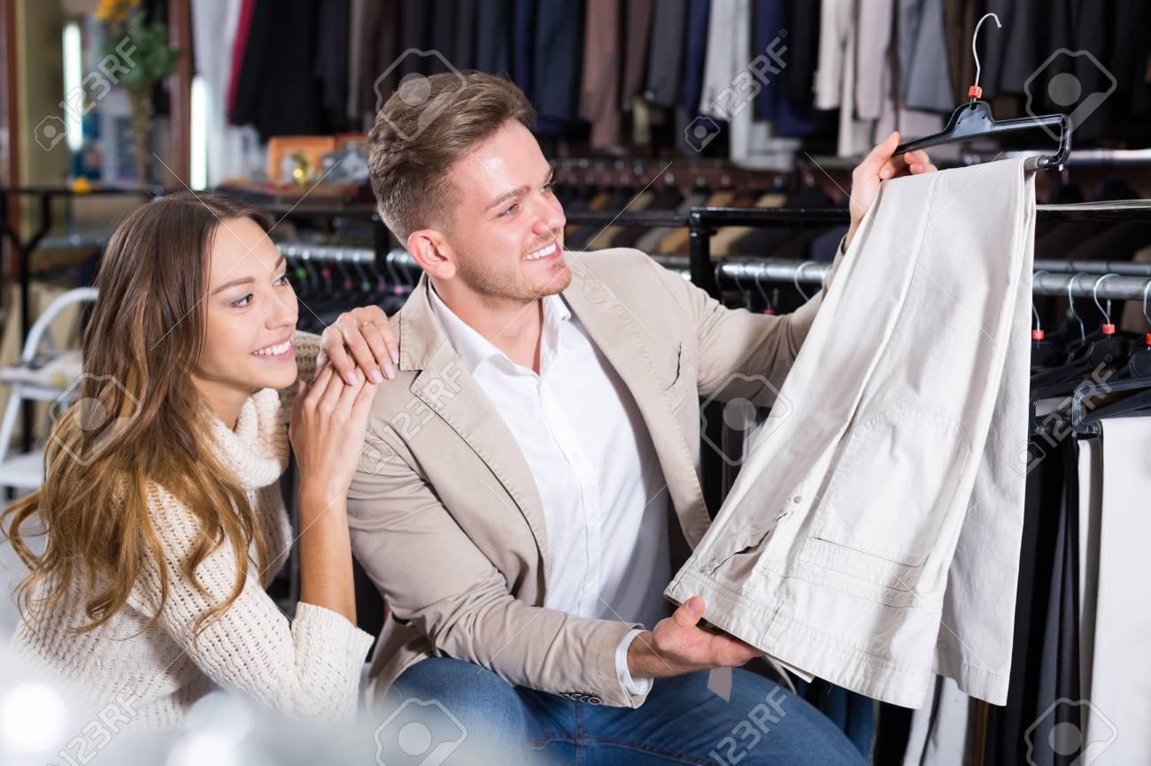 Joven Pareja Hermosa Que Examina Pantalones De Diferentes En La Tienda Para Hombre Panos Fotos Retratos Imagenes Y Fotografia De Archivo Libres De Derecho Image 68911738