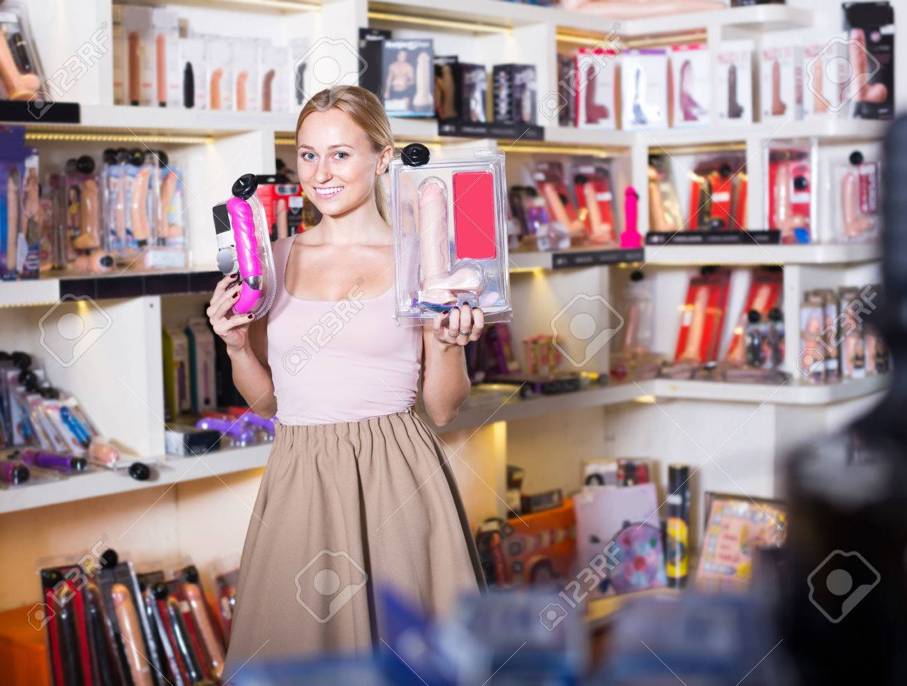 portrait of excited smiling young woman choosing big dildo in