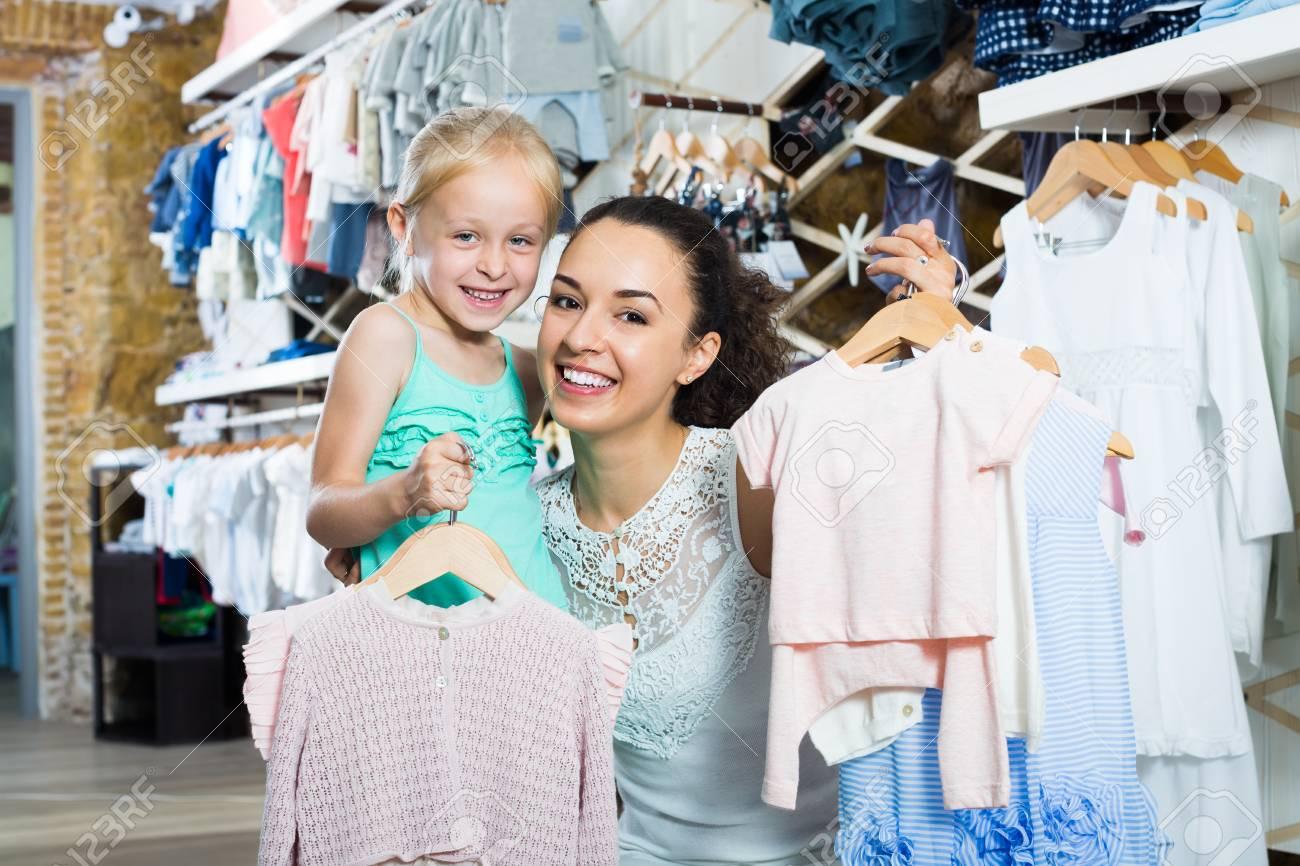 Mujer Feliz Con Niño Pequeño Con Ropa En Boutique De Prendas De Vestir Para Niños