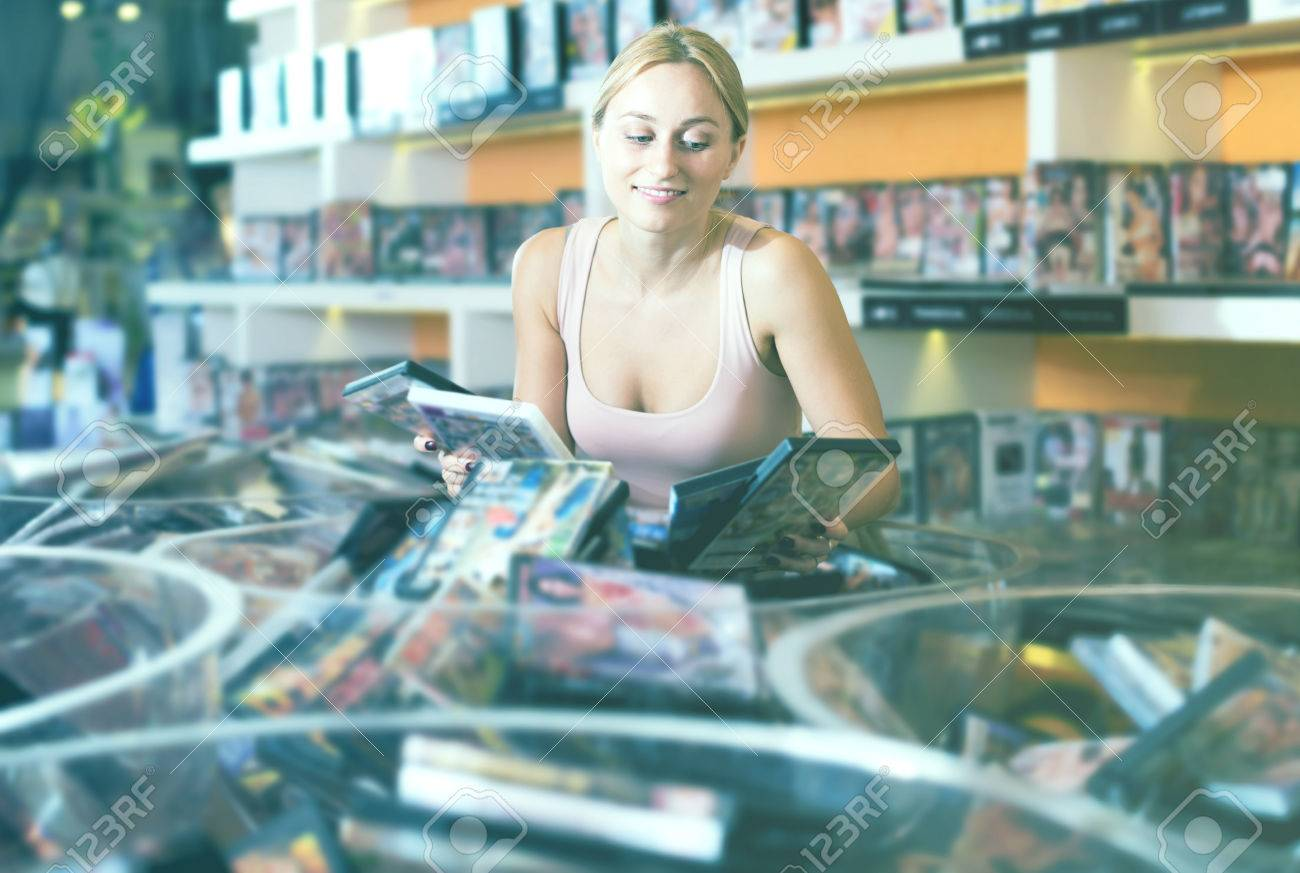 Smiling adult woman buying erotic films in sex shop Stock Photo - 71753922