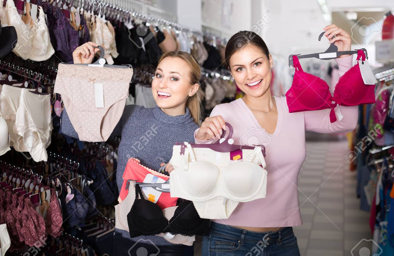 e596b3ba1 two happy russian female customers holding bras and panties in hands in underwear  store Stock Photo