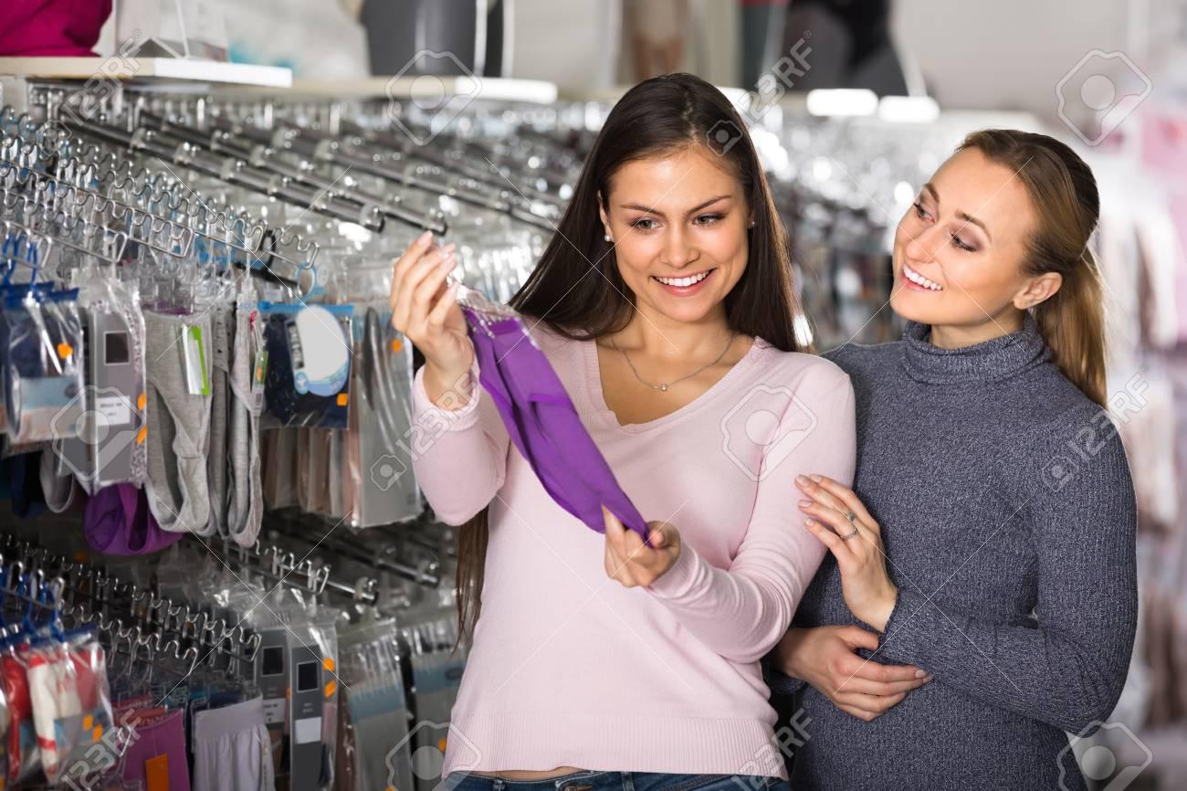 edb9fc8368c0 Dos amigos femeninos sonrientes que eligen cómodas bragas de la ropa  interior en la tienda
