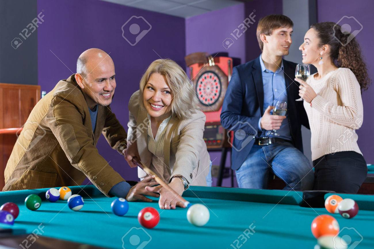 Group of cheerful charming positive friends playing billiards and smiling in night club Banque d'images - 72699427