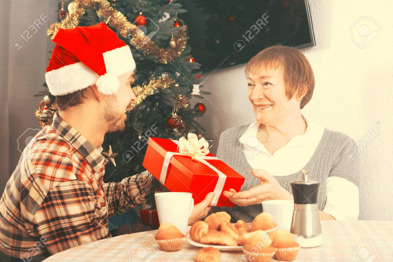 elderly mother and her son exchange holiday christmas gifts at festive table stock photo 73220067