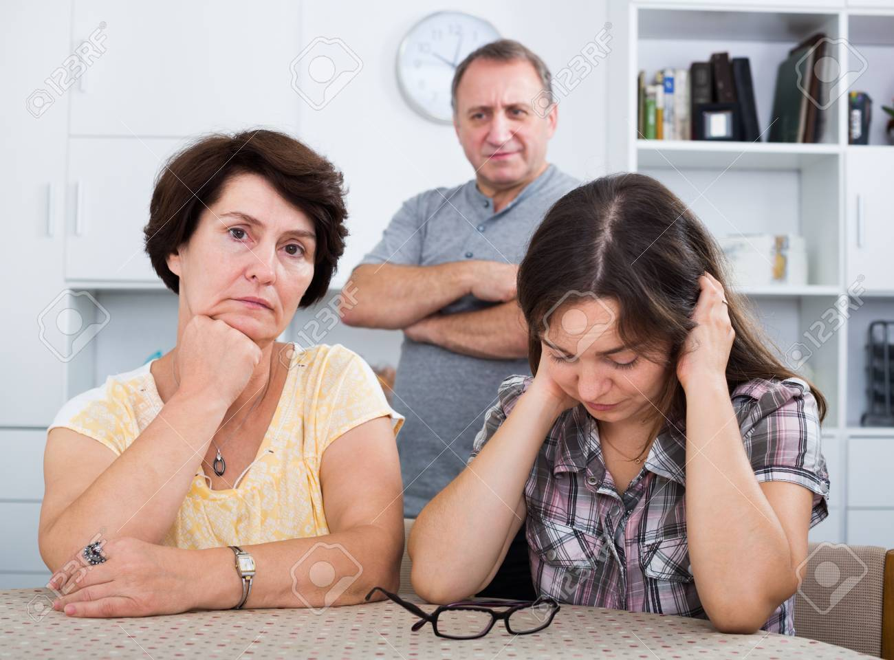Sad young woman talking to her mature parents and getting help