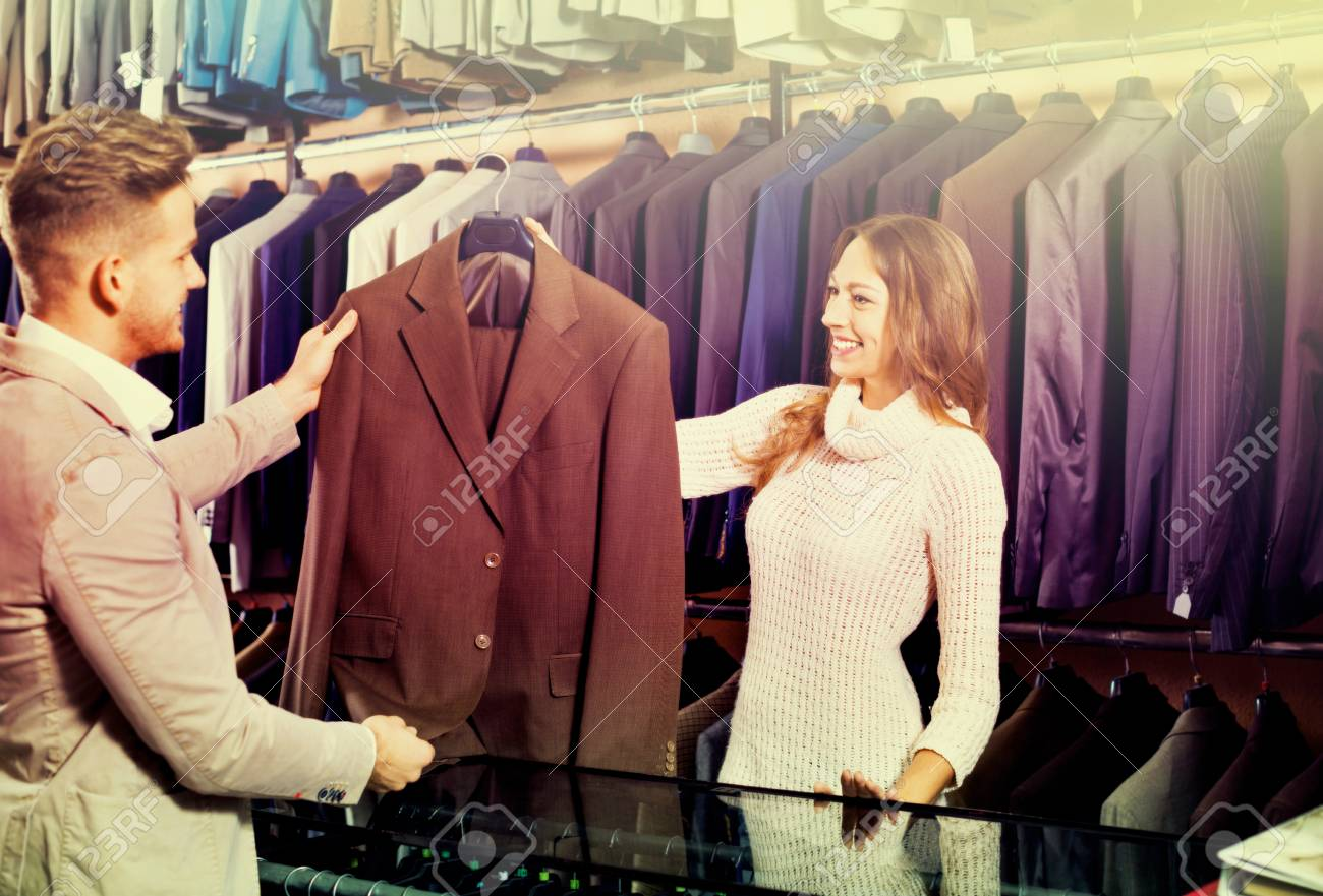 Positive female shop assistant helping customer to choose suit