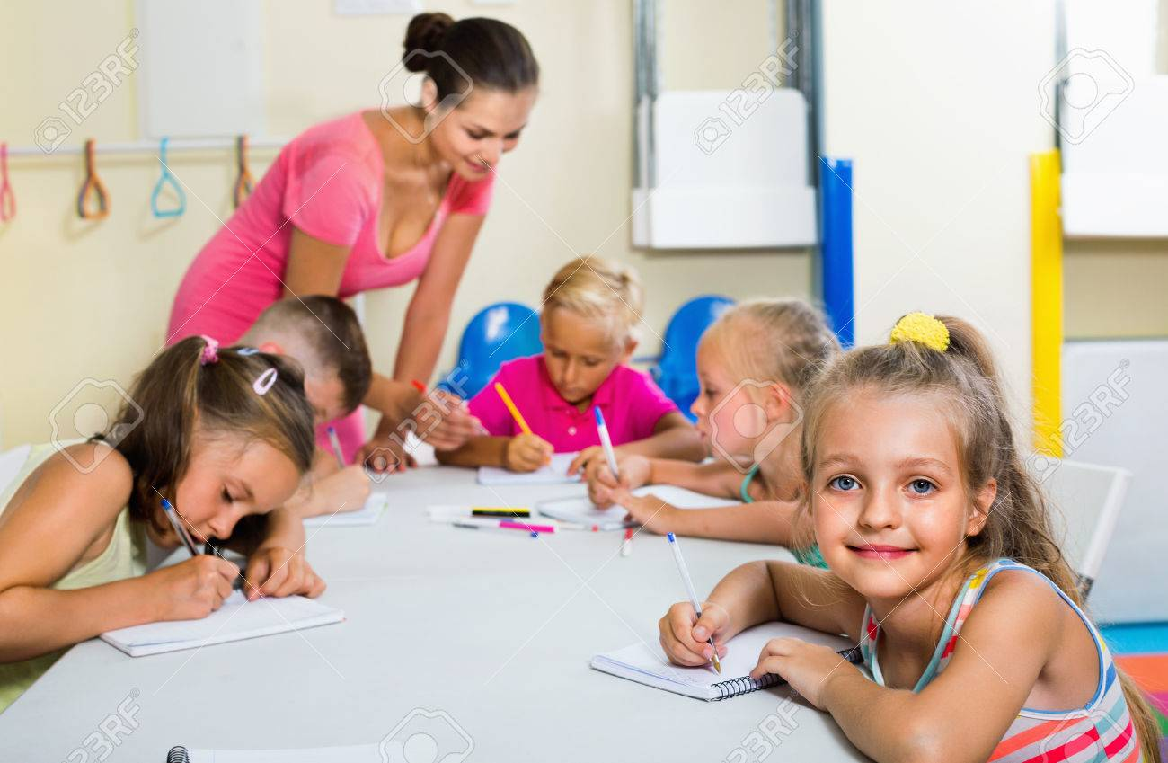 glad diligent kids writing together with tutor at school class