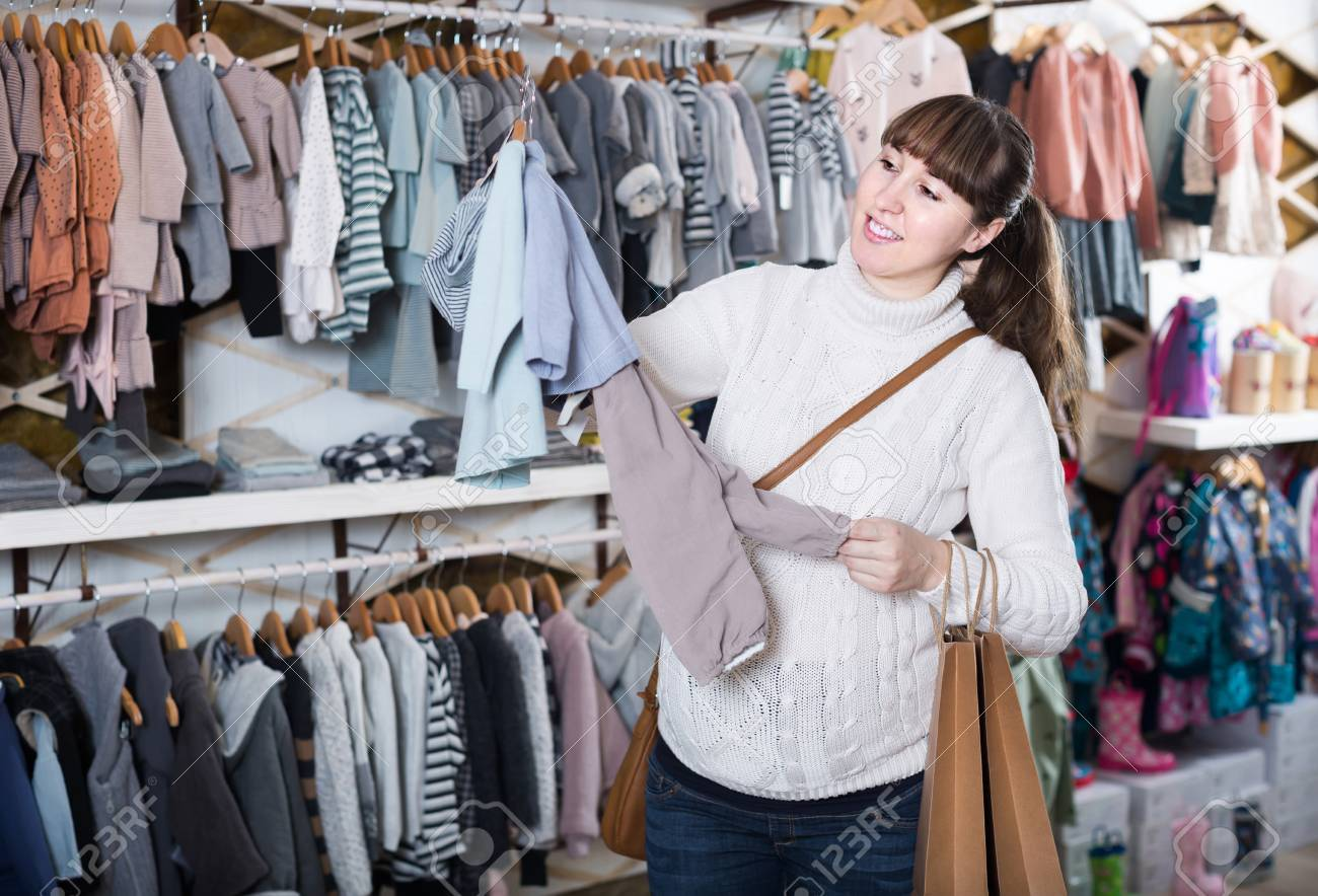e79cee44e Feliz mujer embarazada europeo decidiendo ropa para bebé en tienda de ropa  para niños Foto de