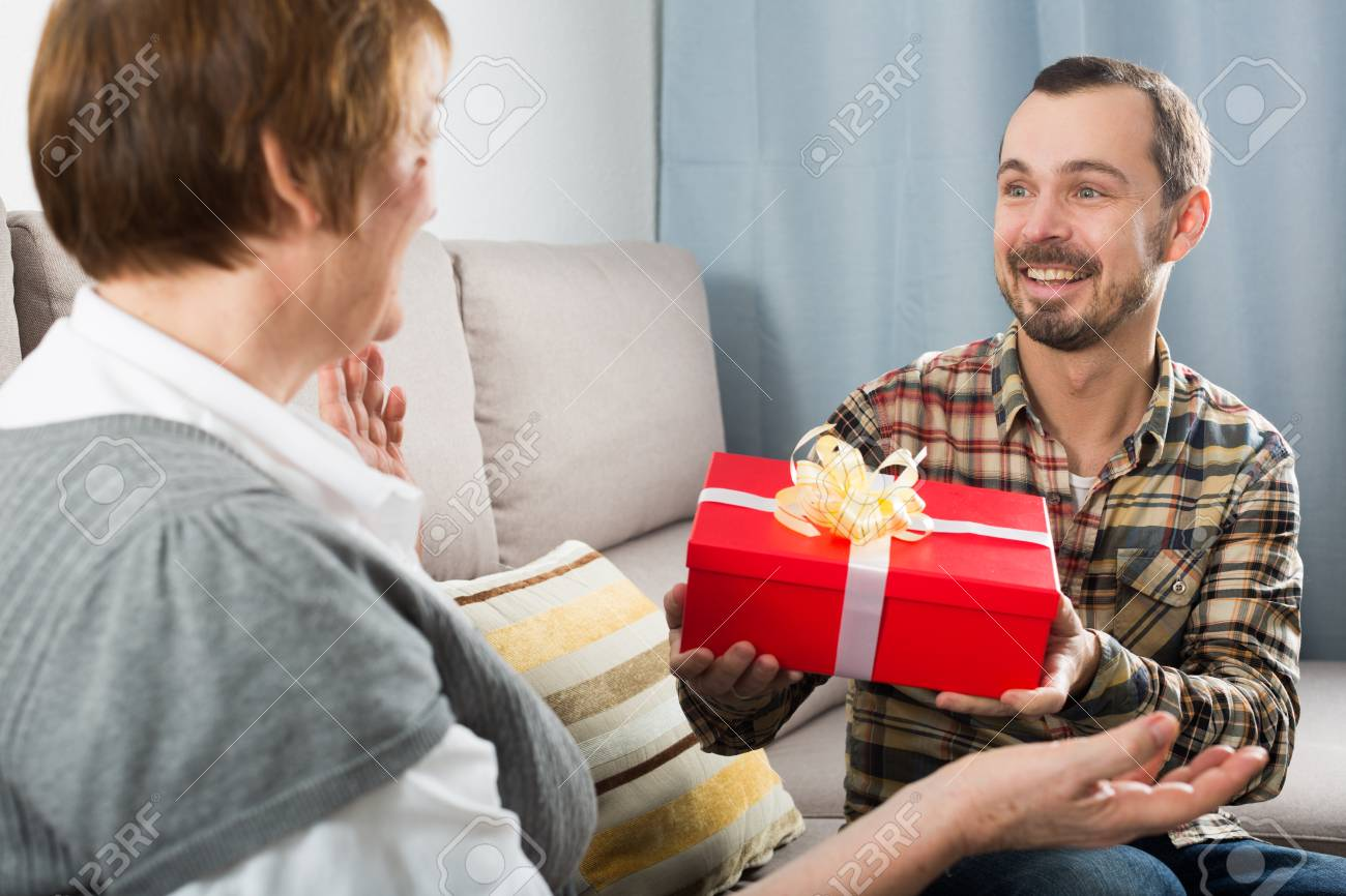 Son Gives Gift In Red Box To His Elderly Mother For Birthday Stock Photo