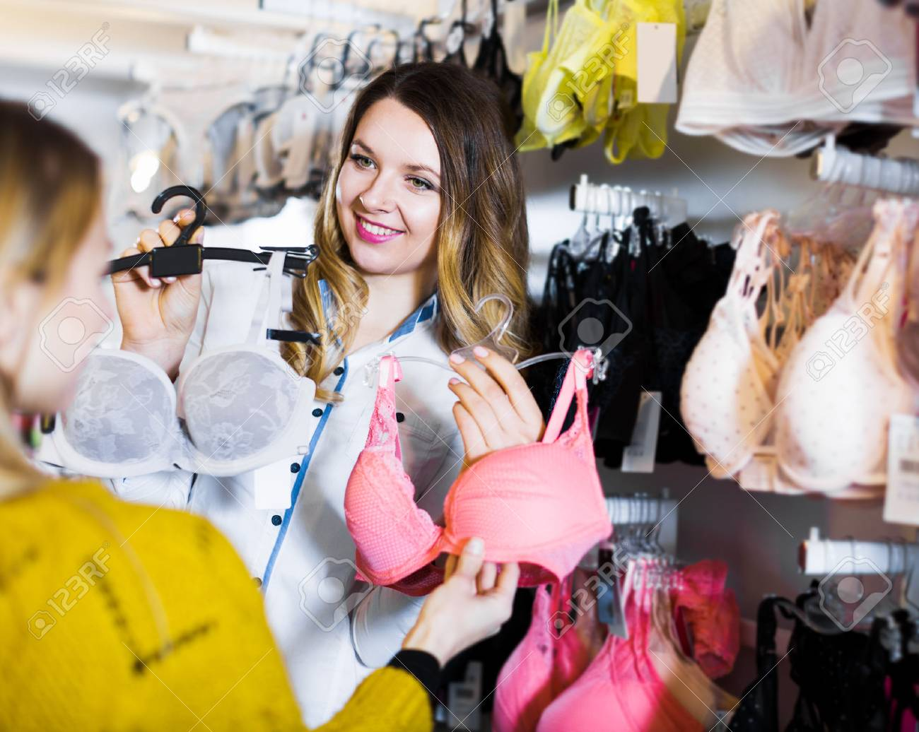 a085b4ada7 Smiling young woman seller assisting woman in choosing bra in underwear  store Stock Photo - 77765840