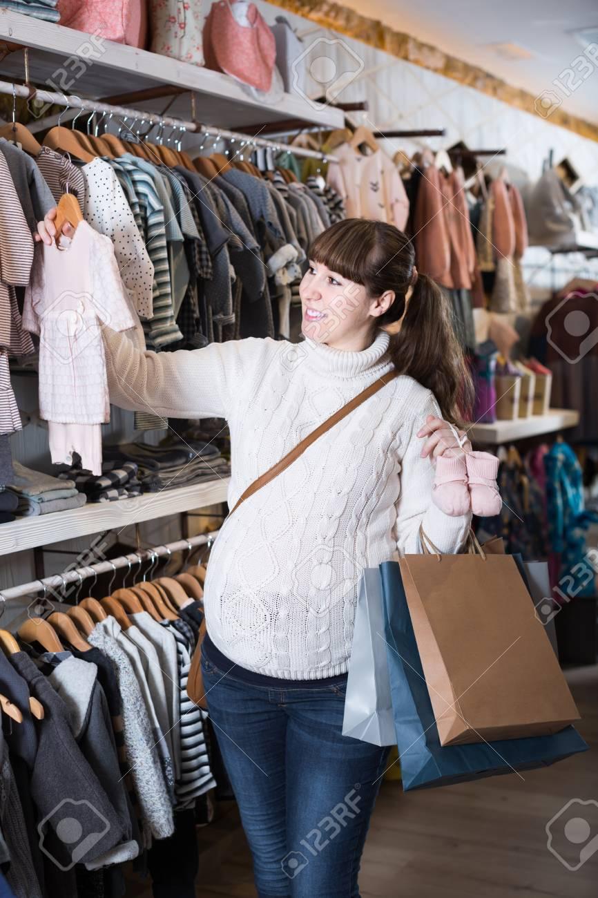 009c9a163 Foto de archivo - Mujer embarazada europea positiva mostrando sus compras  en la tienda de ropa para niños