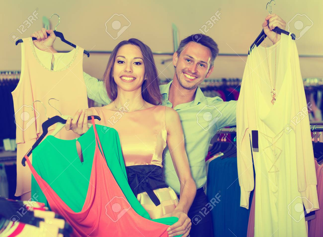 46737b7b33 Family couple is choosing new dresses in women clothes shop. Stock Photo -  78829452