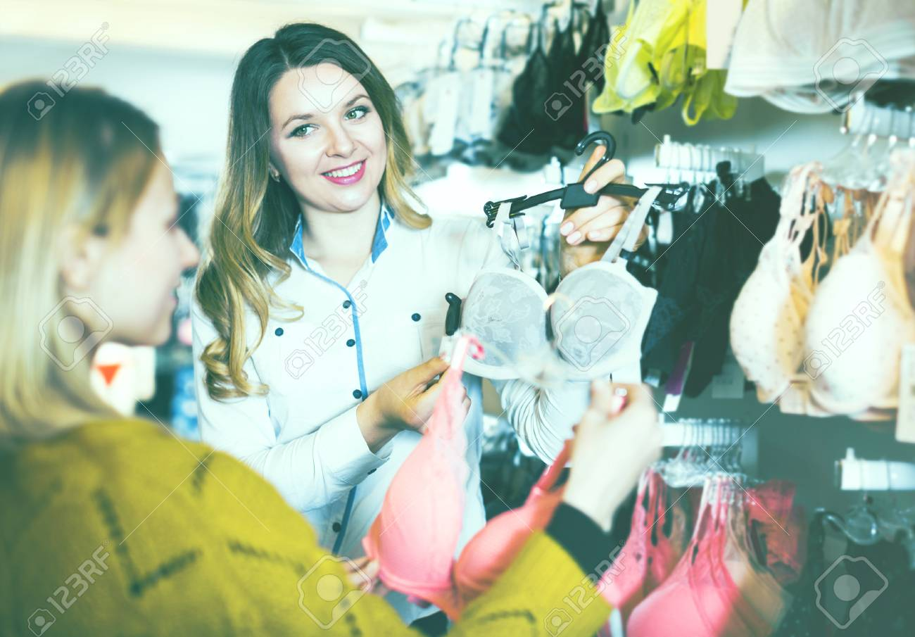 429da60f1c Positive young woman seller assisting woman in choosing bra in underwear  store Stock Photo - 79632931