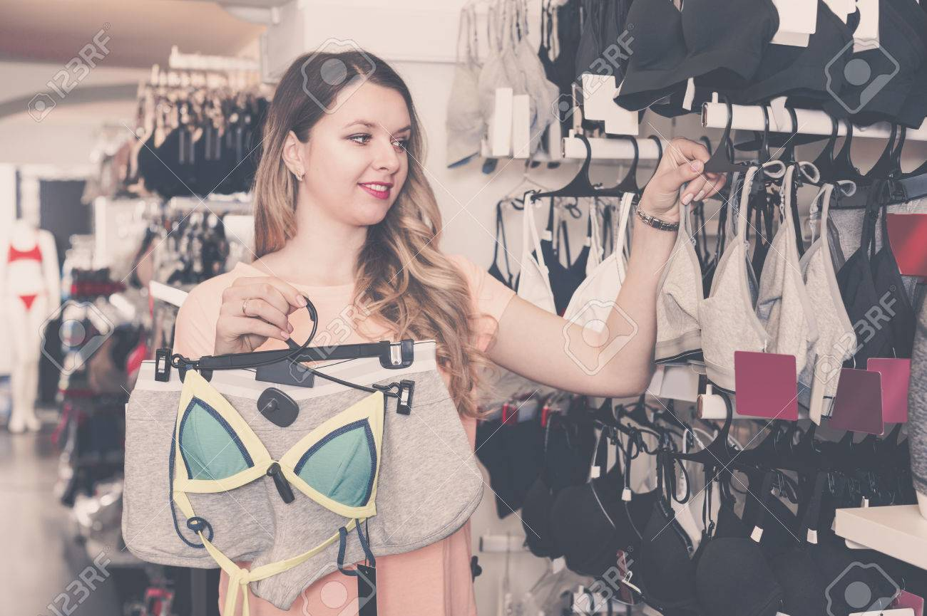ad7df305c82 Stock Photo - Young female is choosing sports underwear in lingerie shop.