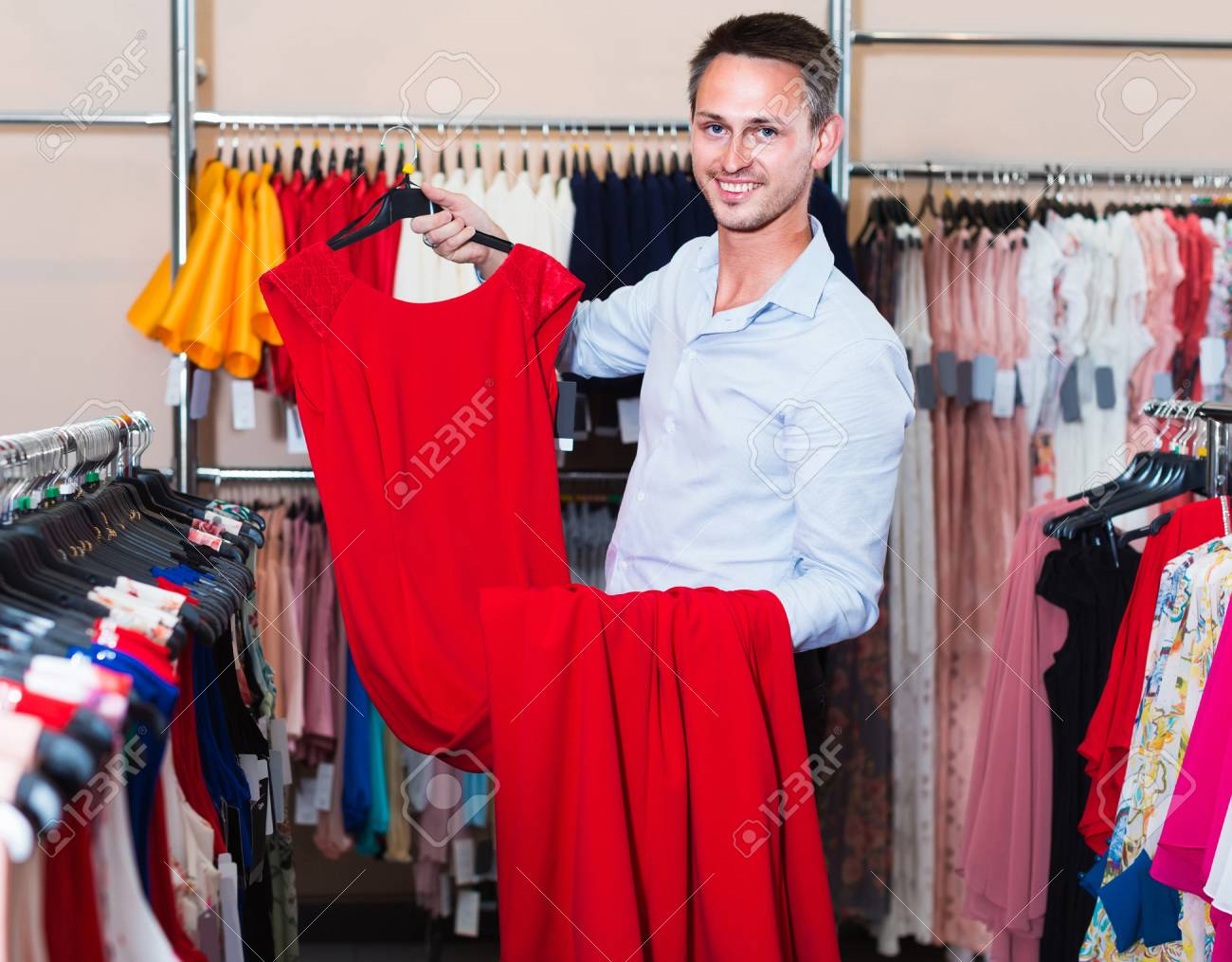985abb6f60 cheerful french man smiling and offering dresses in women clothing..