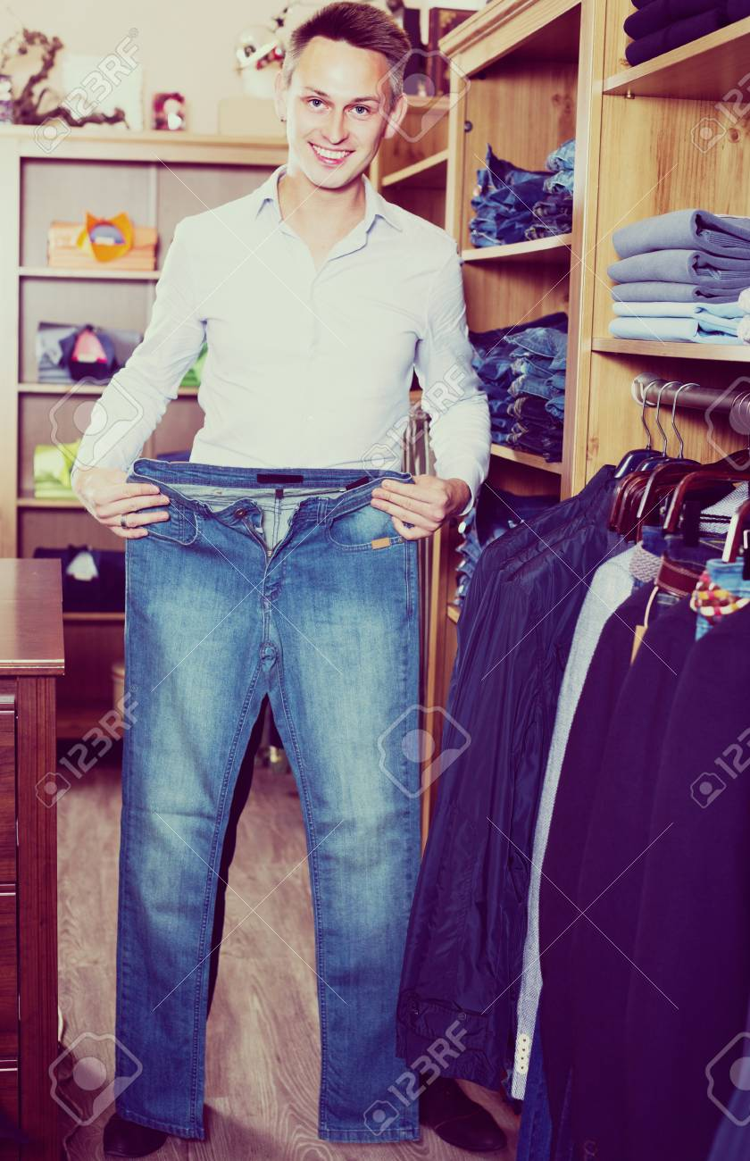 81c3d52e Young man is choosing on new jeans in men's clothes store. Stock Photo -  79832070