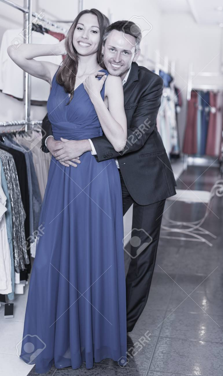 f8a89e3e58 Portrait of happy family couple posing together in the female clothes shop.  Focus on both