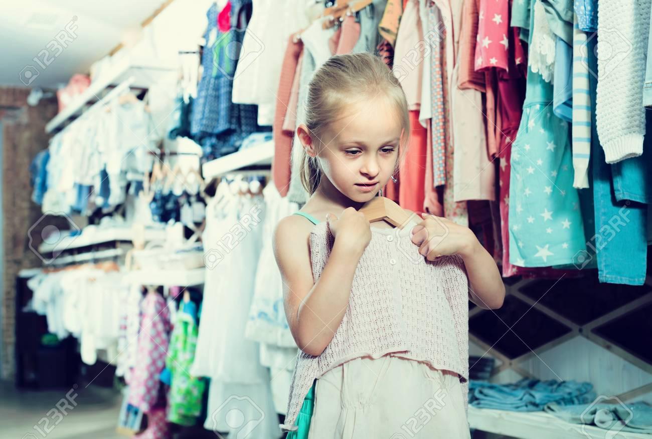 f97bf158123 Foto de archivo - Niña sosteniendo nuevo vestido en manos en ropa de niños  boutique