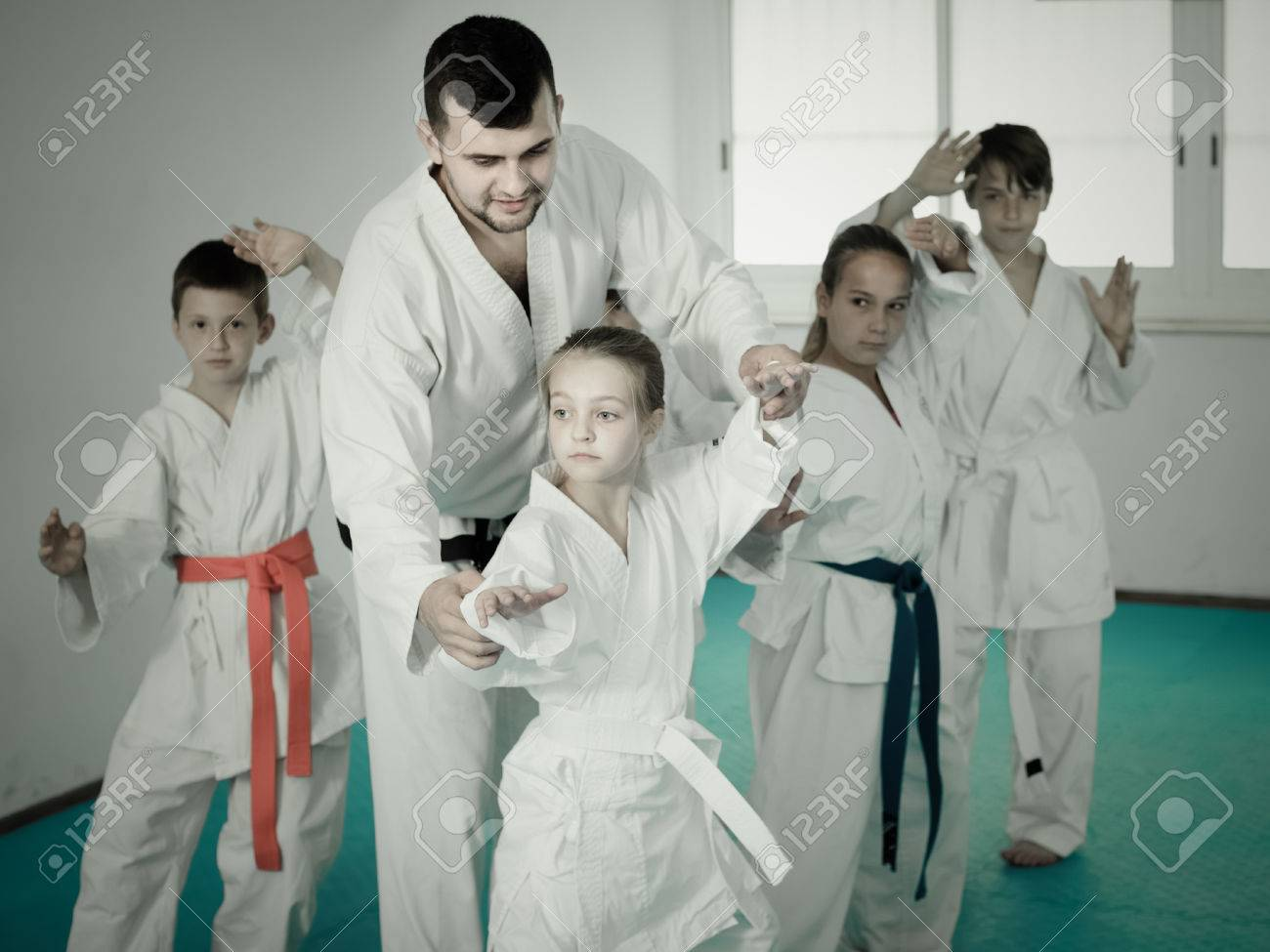 Young children doing karate kicks with male coach during karate