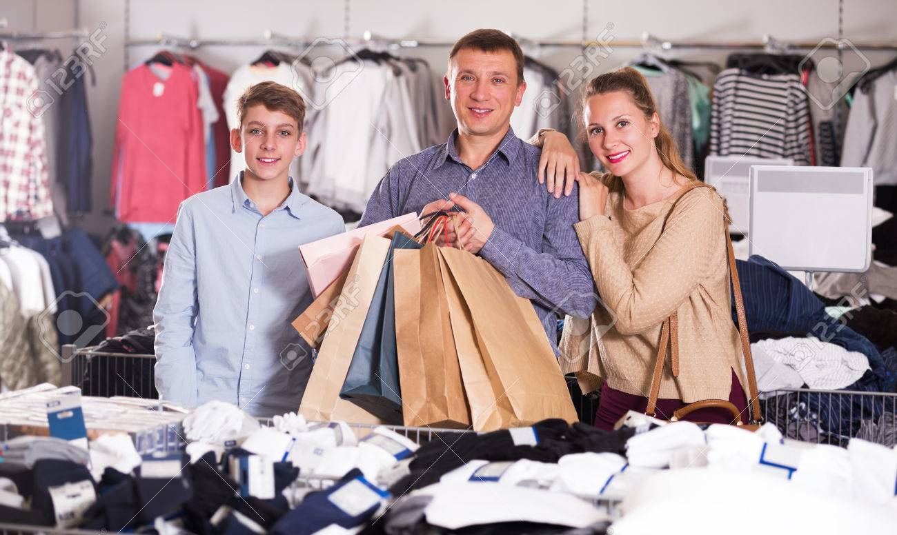 e98b63208e Family couple with teen displaying shopping bags with purchases in clothes  store Stock Photo - 81380452