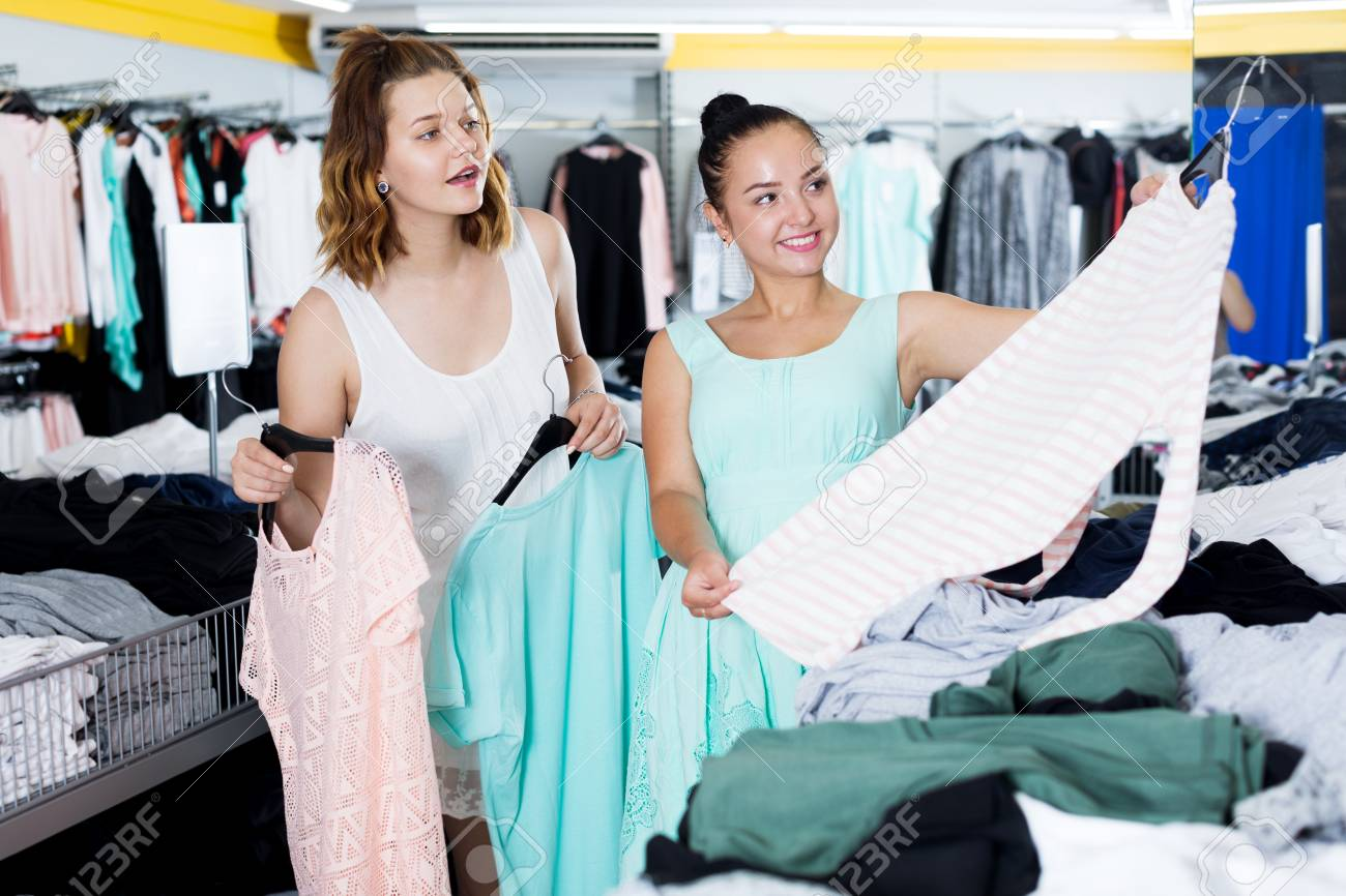 90cb98bccb391 Smiling young women shopping at the clothing store Stock Photo - 83666893