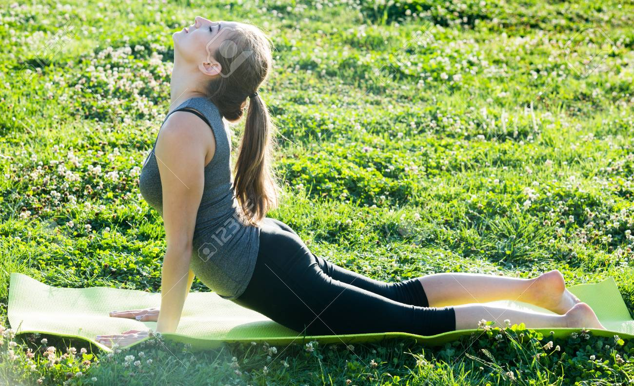 Stock Photo   Young Czech Female Doing Yoga Poses On Sunny Morning In The  Green Garden