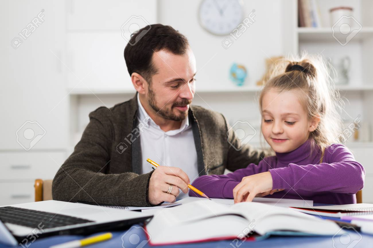 Father helping his child to do homework at home - 82420595
