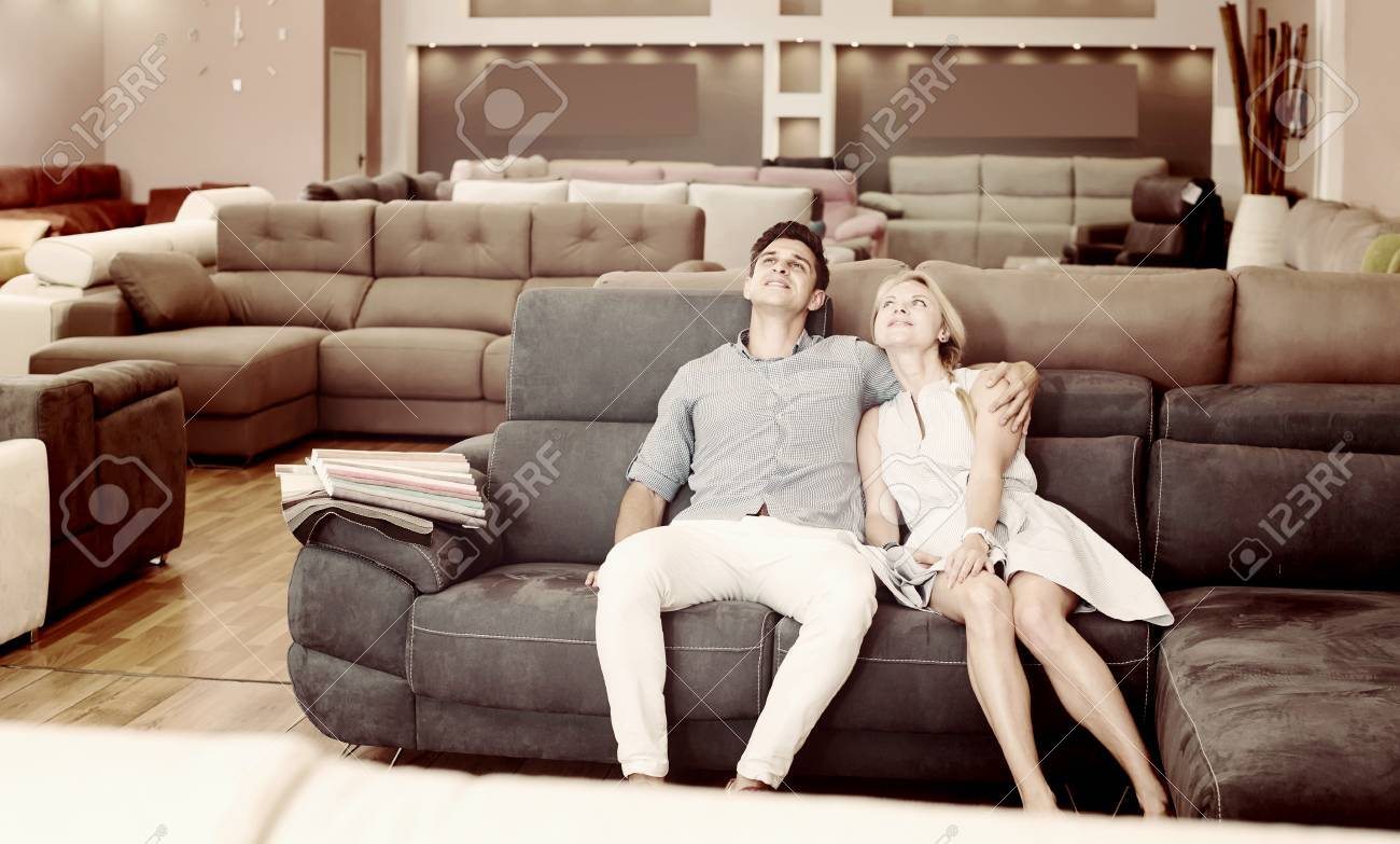 Portrait Of A Couple Who Are Choosing New Sofa Transformer In The Store.  Stock