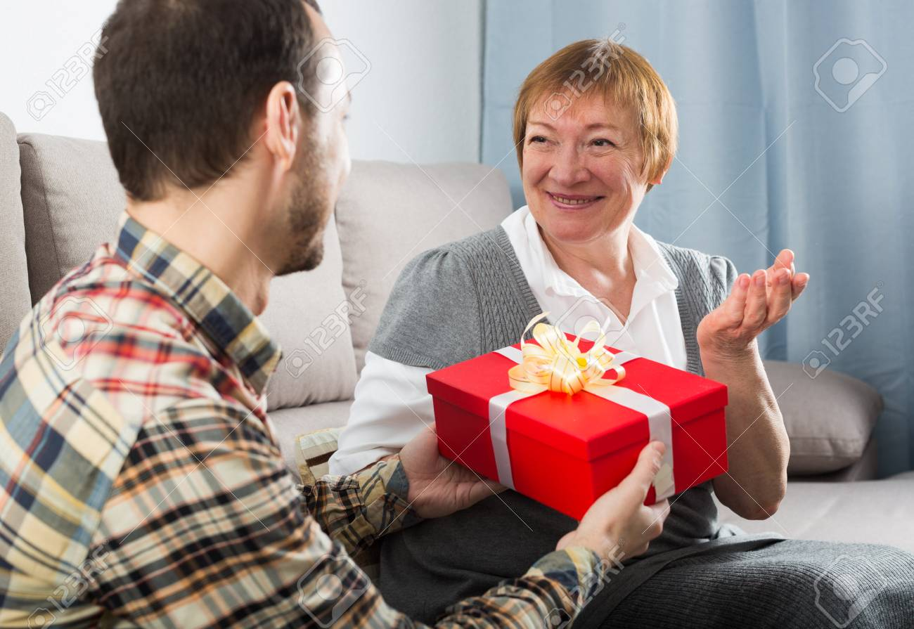 Son Gives Holiday Gift Box To Elderly Mother At Home Stock Photo
