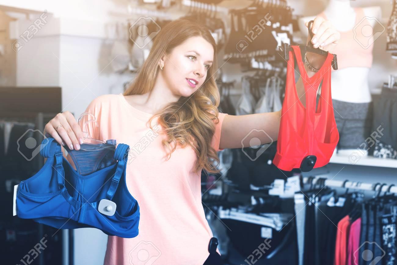 3d689d40d11 Positive girl customer choosing sports underwear in lingerie store Stock  Photo - 83811098