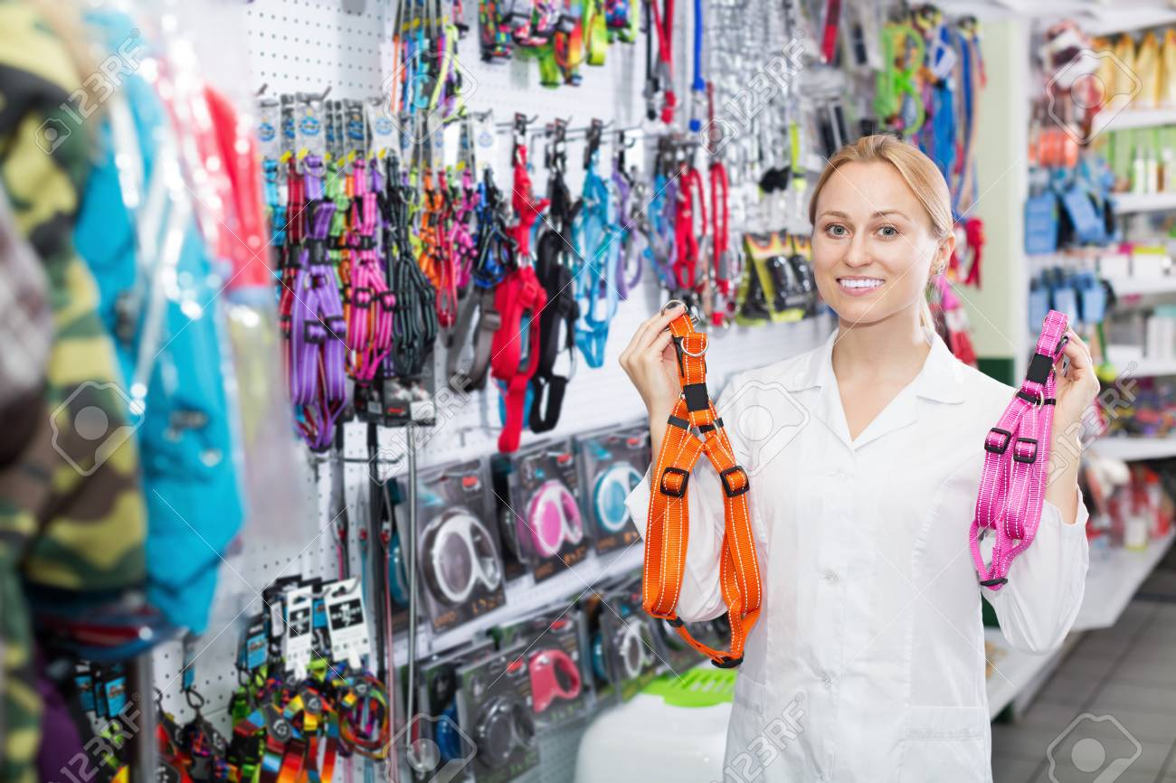 Smiling Girl Assistant Advising On Leashes For Pets In Pet Shop Stock  Photo, Picture And Royalty Free Image. Image 84060618.
