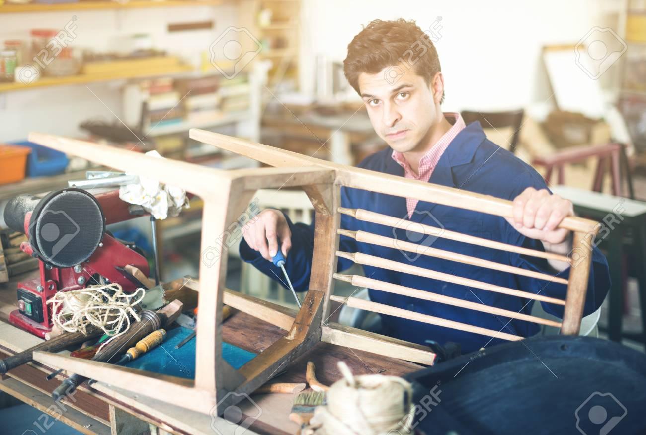 Carpenter working in repair studio and repairing broken wooden
