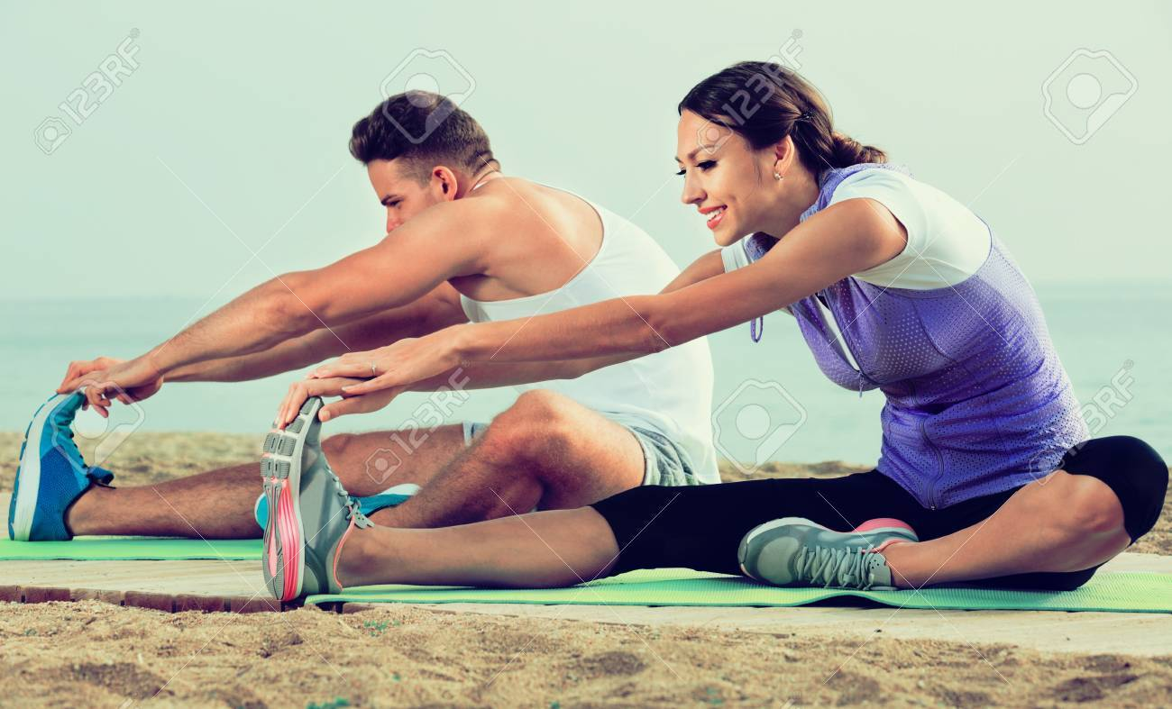 Cheerful Positive Couple Training Yoga Poses Sitting On Beach Sunny Morning Stock Photo