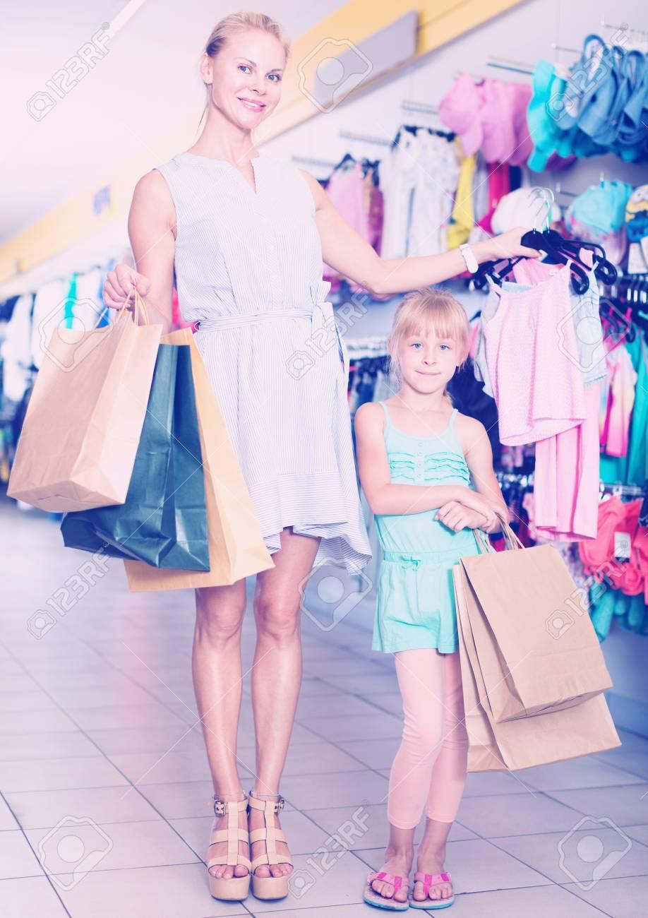 ad3df9815fb7 Alegre sonriente mujer con packs y niña comprar ropa en la tienda de  vestidos