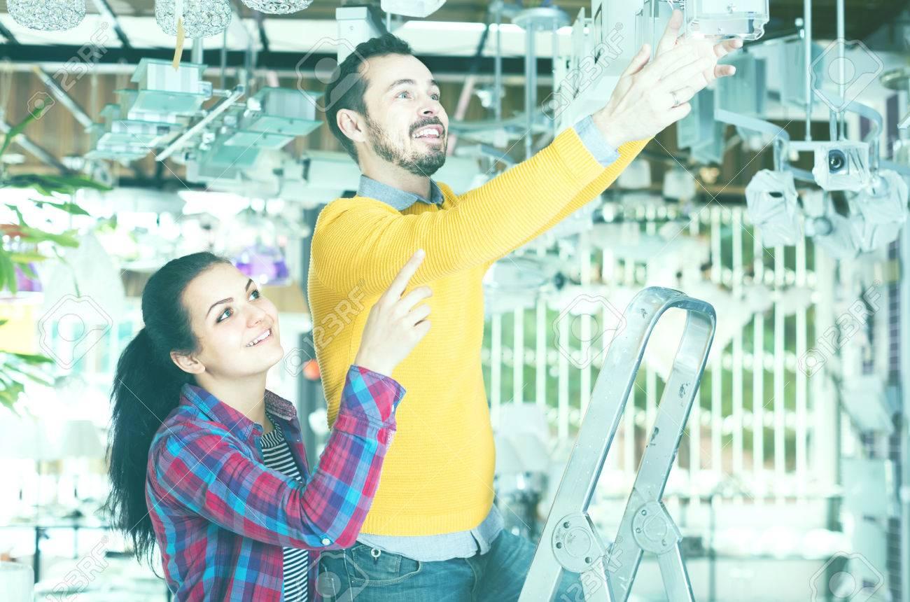e12387ff9 Foto de archivo - Hombre americano feliz y una niña en el viejo tamaño de la  vendimia enorme que selecciona la lámpara de café de color rojo para la casa