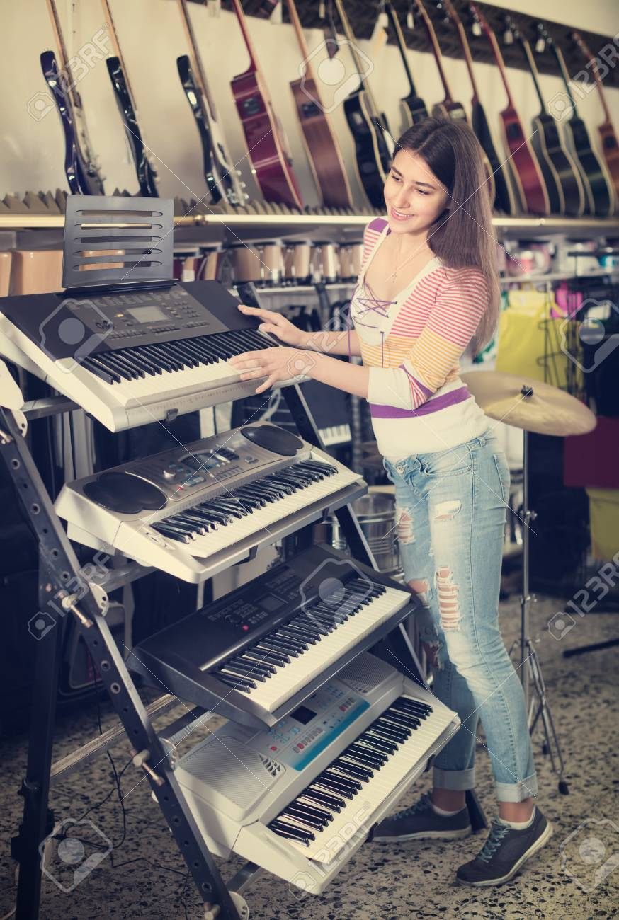 Smiling teenage girl choosing synthesizer in store