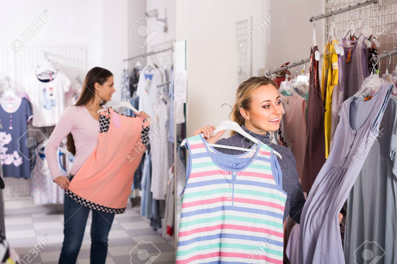 ccb709c1c204 Stock Photo - Two joyful young women selecting comfortable sleepwear  together in lingerie department