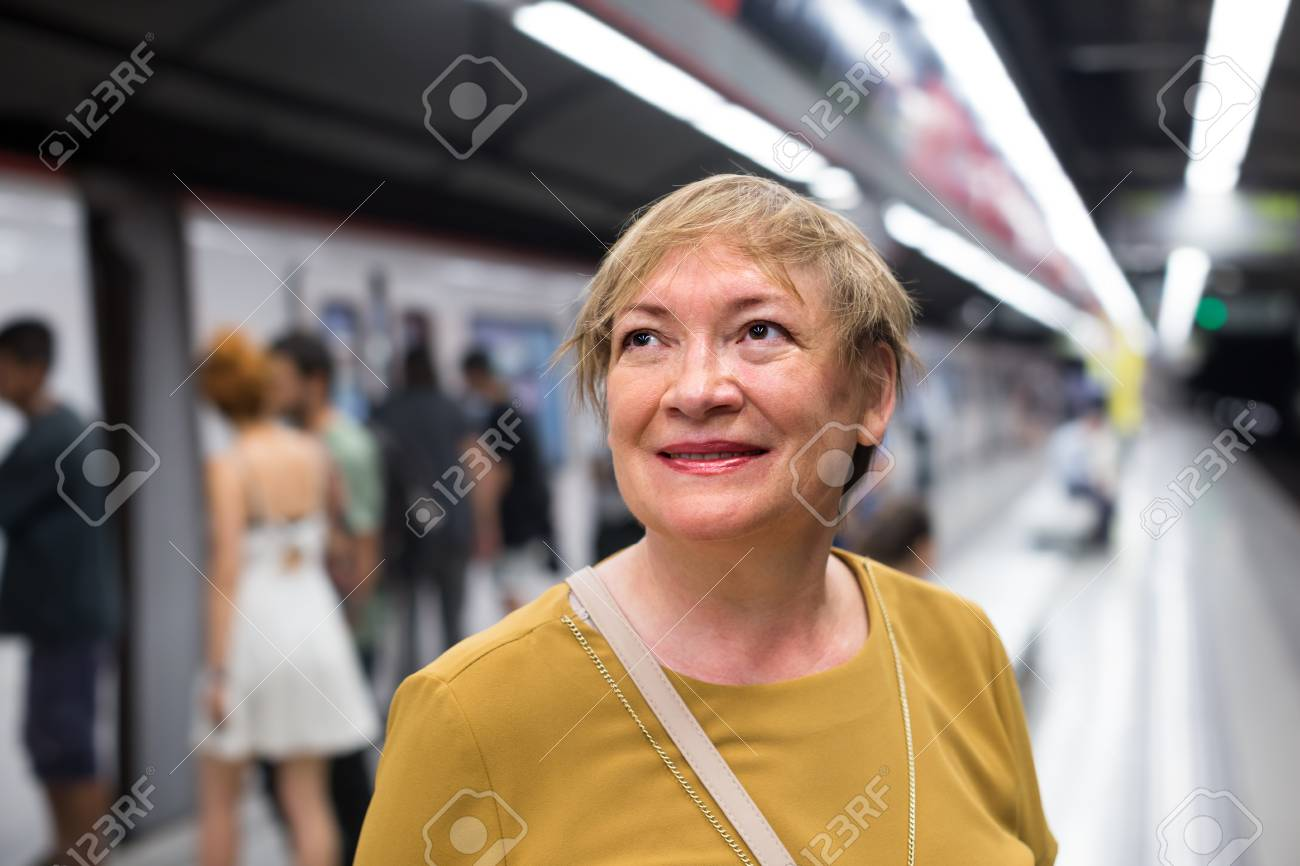 active female mature passenger riding underground in town stock