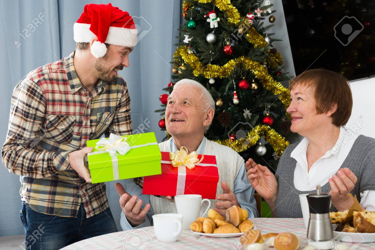 elderly parents take gifts from son for christmas at festive table stock photo 87981895