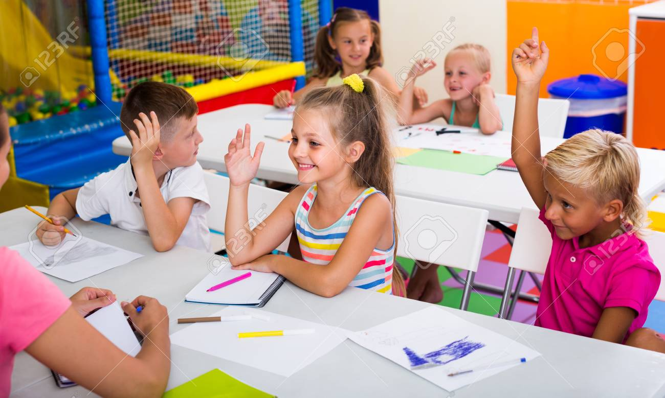 Joyful Primary School Kids Sitting At School Class And Listening ...