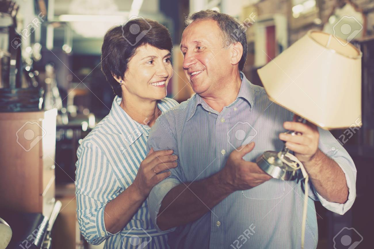 positive mature couple is shopping the old lamp for home in the