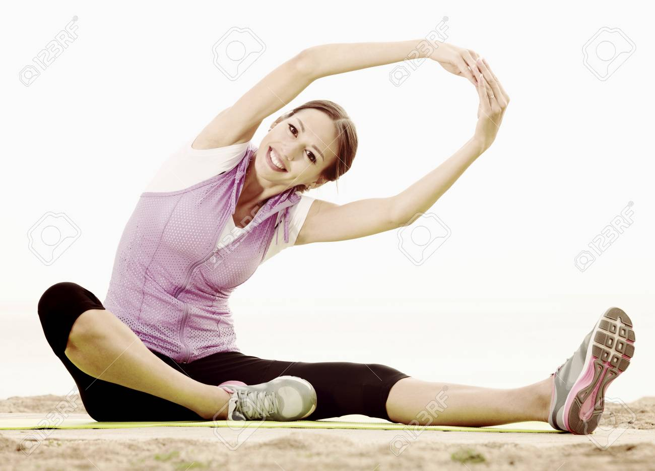 Cheerful Young Woman Training Yoga Poses Sitting On Beach Sunny Morning Stock Photo